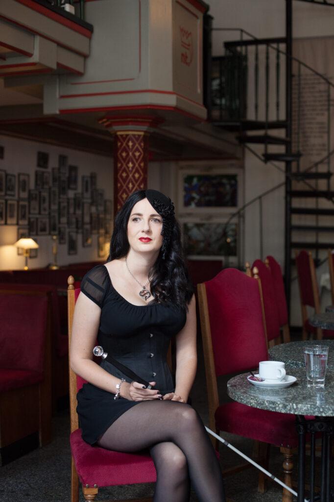 Jennifer Sonntag sitzt mit übereinander geschlagenen Beinen auf einem rot gepolsterten Stuhl an einem kleinen Tisch, auf dem eine Kaffeetasse und ein Wasserglas stehen. Ihr Blick scheint an der Kamera vorbei in die Ferne zu schweifen. Die Lippen sind geschlossen und in einem kräftigen Rotton geschminkt. In den Händen mit den schwarz lackierten Fingernägeln hält sie einen Blindenstock mit einem eleganten langen schwarzen Griff, der oben mit einem großen Kristall verziert ist. Sie trägt ein kurzes schwarzes Kleid mit kurzen Ärmeln und eine schwarze Corsage. Die langen schwarzen Haare fallen in leichten Wellen. Auf dem Kopf trägt sie einen kleinen schwarzen Fascinator (ein kleiner Hut, der ins Haar gesteckt wird), der mit Blüten und Blätterranken aus schwarzem Satin verziert ist. Um den Hals trägt sie eine Kette mit einem silbernen kreisrunden Anhänger, um den sich eine schwarze Schlange windet.